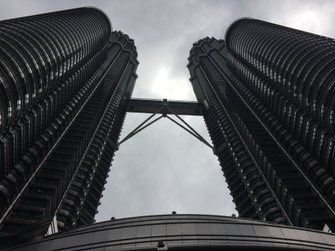 Staring at the bottom of the Petronas towers, up to the sky bridge and cloudy sky.